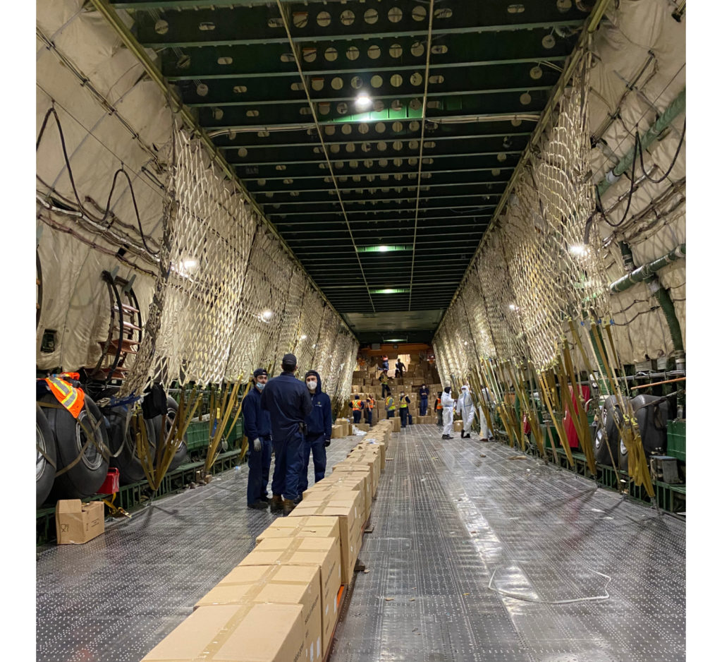 The team unloading the aircraft reverted to placing 16 rollers on the ground and sliding the boxes along the chain and into the back of transport trucks. Nolinor Aviation Photo