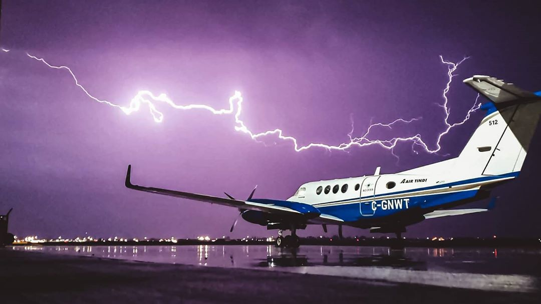 An Air Tindi Beech King Air 200 watches on as lightning fills the sky. Photo submitted by Cameron Barfoot (Instagram user @barfoot12) by tagging @skiesmag.