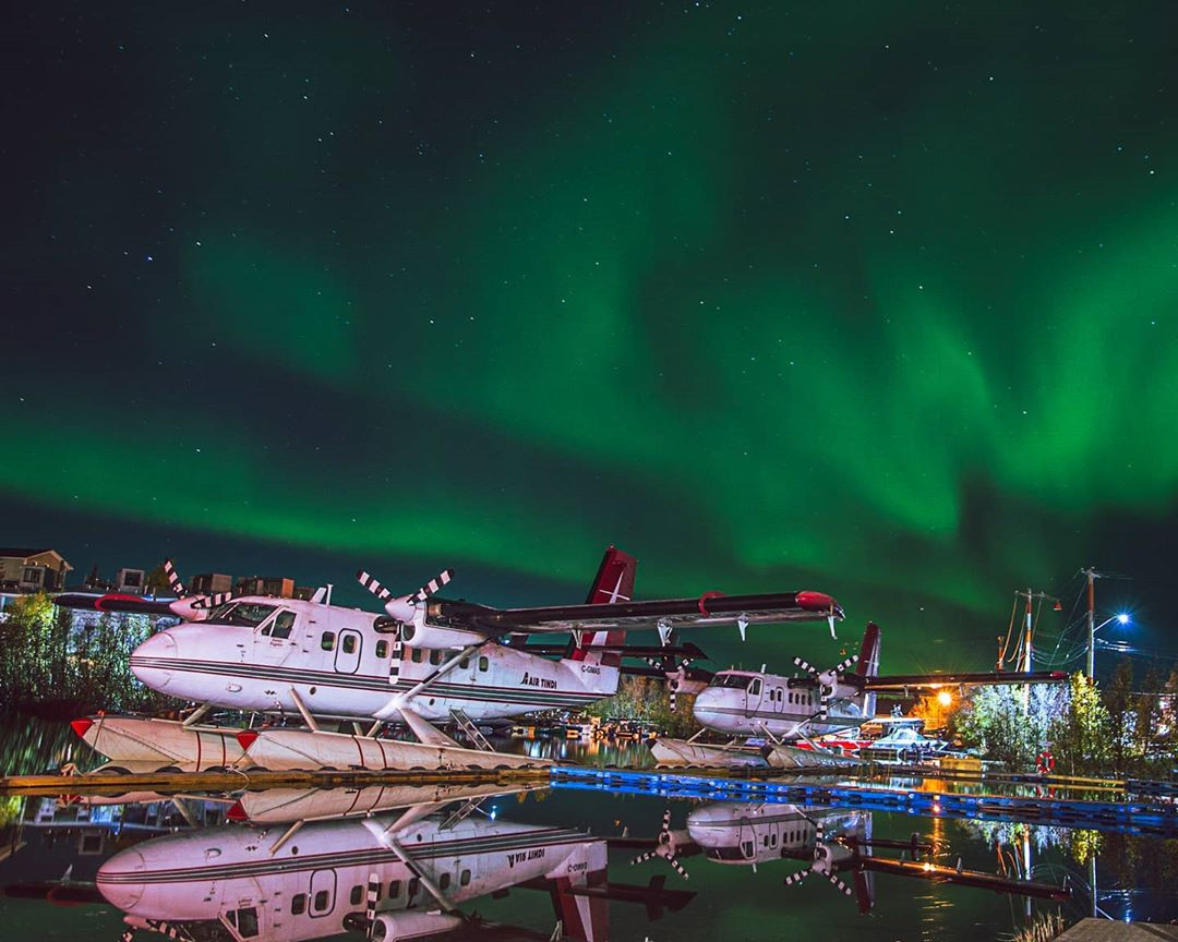 A pair of Air Tindi Twin Otters under the Northern Lights in the Northwest Territories. Photo submitted by Cameron Barfoot (Instagram user @barfoot12) using #skiesmag.